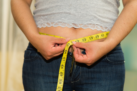 waistline: Closeup womans stomach with shirt lifted up, wearing jeans, measuring waistline using measure band, weightloss concept. Stock Photo