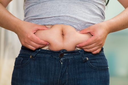excessive: Closeup womans stomach wearing jeans, grabbing onto excessive fat using fingers, belly button revealed, weightloss concept . Stock Photo