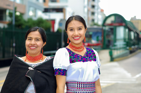 ecuadorian: Beautiful hispanic mother and daughter wearing traditional andean clothing, waiting for bus at public station while posing together, smiling happily, outdoors environment. Stock Photo