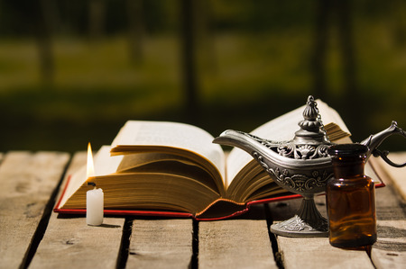 genie in a bottle: Thick book lying open on wooden surface, Aladin lamp and wax candle sitting next to it, beautiful night light setting, magic concept shoot.