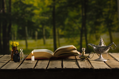 genie in a bottle: Thick book lying open on wooden surface, small brown bottle with flowers, Aladin style lamps and wax candle next to it, magic concept shoot.