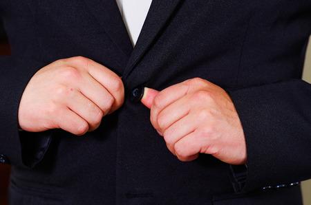 vistiendose: área del pecho del hombre del primer uso de traje formal y corbata, los botones de ajuste de la chaqueta con las manos, los hombres conseguir concepto vestido.