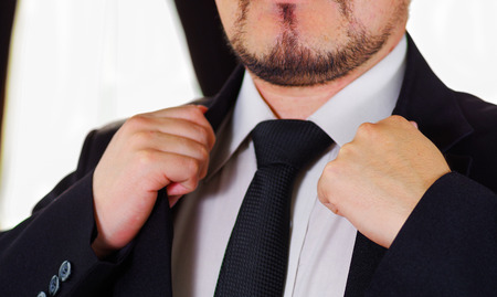 vistiendose: Closeup mans chest area wearing formal suit and tie, adjusting jacket collar using hands, men getting dressed concept.