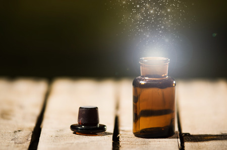 top animated: Small brown medicine bottle for magicians remedy, animated star dust coming out from top ,sitting on wooden surface.