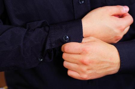 vistiendose: Closeup mans arm wearing suit, adjusting cufflinks using hands, men getting dressed concept. Foto de archivo