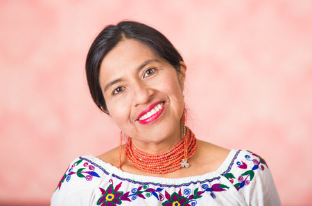 Headshot beautiful hispanic mother wearing traditional andean clothing, posing happily while smiling to camera, pink studio background.