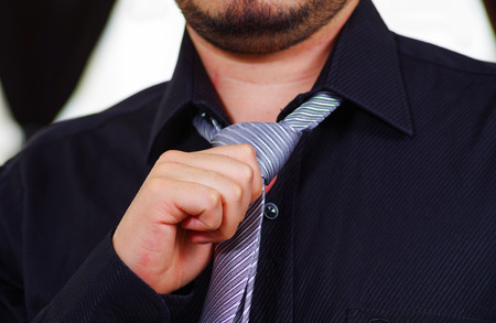 vistiendose: Closeup mans chest wearing white shirt, tying tie using hands, face partly visible, men getting dressed concept. Foto de archivo