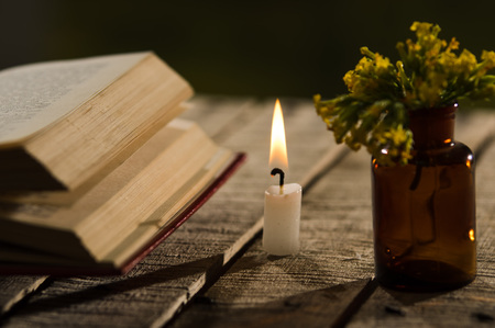 Thick book lying open on wooden surface, wax candle and small bottle with yellow flowers sitting next to it, beautiful night light setting, magic concept shoot. Stock Photo