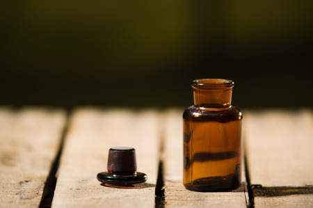 genie in a bottle: Small brown medicine bottle for magicians remedy, black cap lying next to it on wooden surface. Stock Photo