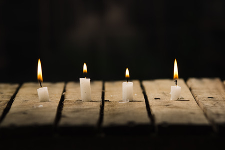 genie in a bottle: Four white wax candles sitting on wooden surface burning with black background, beautiful light setting.