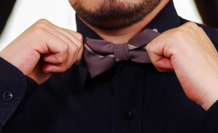 vistiendose: Closeup mans chest wearing white shirt, tying bowtie using hands, face partly visible, men getting dressed concept.
