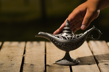 Beautiful antique metal lamp in true Aladin style, hand touching it gently, sitting on wooden surface. Stock Photo