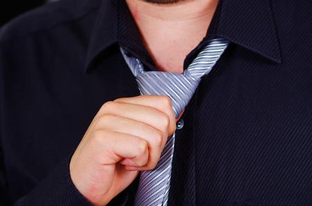 vistiendose: pecho del hombre del primer con camisa blanca, que ata el lazo usando las manos, la cara visible en parte, los hombres conseguir concepto vestido. Foto de archivo