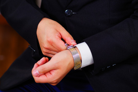 vistiendose: el uso de traje, el ajuste de reloj de pulsera de plata usando las manos, los brazos de los hombres del hombre del primer concepto de conseguir vestidos.
