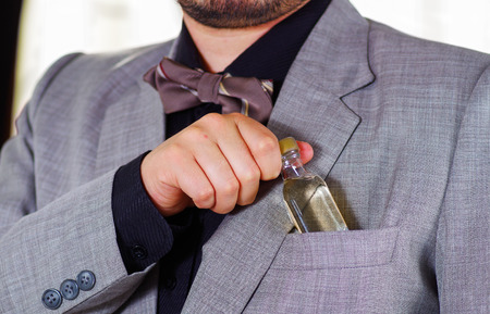 vistiendose: Closeup mans chest area wearing formal suit and tie, placing small liquor bottle in jacket pocket, men getting dressed concept.