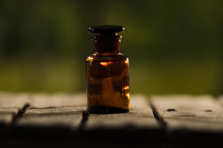genie in a bottle: Small brown medicine bottle for magicians remedy sitting on wooden surface, beautiful night light setting, magic concept.