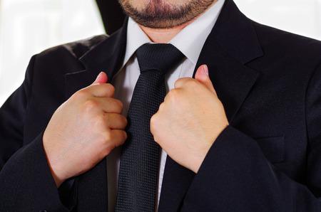 vistiendose: área del pecho del hombre del primer uso de traje formal y corbata, ajustando cuello de la chaqueta con las manos, los hombres conseguir concepto vestido.