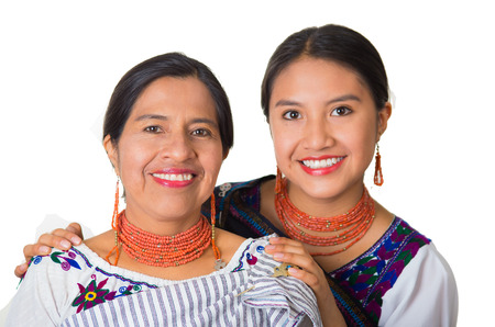 ecuadorian: Beautiful hispanic mother and daughter wearing traditional andean clothing, embracing while posing happily together interacting for camera, white studio background. Stock Photo