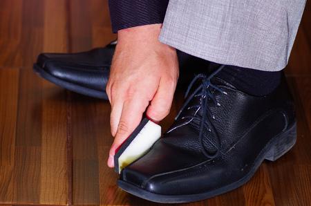 vistiendose: Closeup mans formal black shoes, using sponge to polish leather, men getting dressed concept.