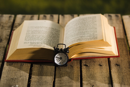 genie in a bottle: Thick book lying open on wooden surface, old fashioned night table clock sitting next to it, magic concept shoot.