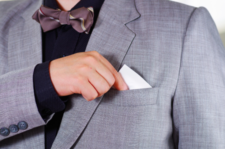 vistiendose: Closeup mans chest area wearing formal suit and tie, placing tissue in jacket pocket, men getting dressed concept.