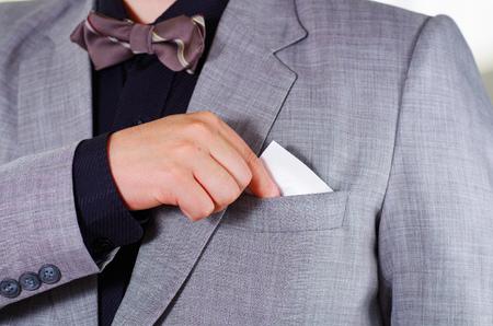 vistiendose: área del pecho del hombre del primer uso de traje formal y corbata, colocar el tejido en el bolsillo de la chaqueta, los hombres conseguir concepto vestido.