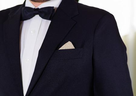 vistiendose: Closeup mans chest area wearing formal suit and bowtie, men getting dressed concept.