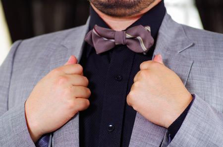 vistiendose: área del pecho del hombre del primer uso de traje formal y corbata de moño, ajustando cuello de la chaqueta con las manos, los hombres conseguir concepto vestido. Foto de archivo