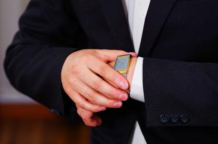 vistiendose: Closeup mans arm wearing suit, adjusting silver wrist watch using hands, men getting dressed concept. Foto de archivo