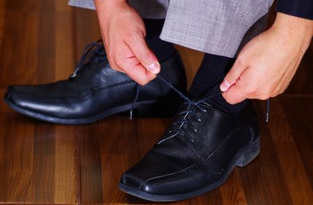 vistiendose: Closeup mans formal black shoes, using hands tying laces, men getting dressed concept.