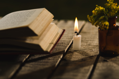 genie in a bottle: Thick book lying open on wooden surface, wax candle and small bottle with yellow flowers sitting next to it, beautiful night light setting, magic concept shoot. Stock Photo