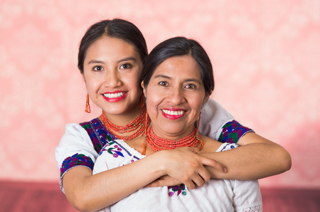 Beautiful hispanic mother and daughter wearing traditional andean clothing, embracing while posing happily together interacting for camera, pink studio background.
