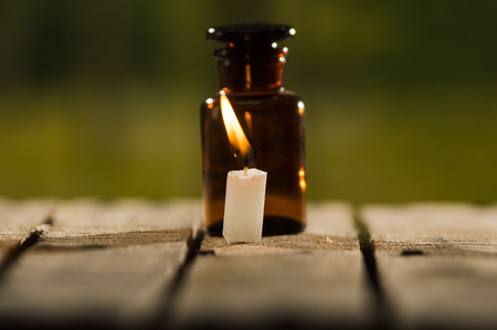genie in a bottle: Small brown medicine bottle for magicians remedy and white wax candle sitting on wooden surface, beautiful night light setting, magic concept.