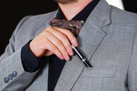 vistiendose: área del pecho del hombre del primer uso de traje formal y corbata, la colocación de la pluma en el bolsillo de la chaqueta, los hombres conseguir concepto vestido. Foto de archivo