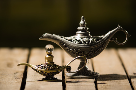 Beautiful antique metal lamp in true Aladin style, smaller model placed next to it, sitting on wooden surface. Stock Photo