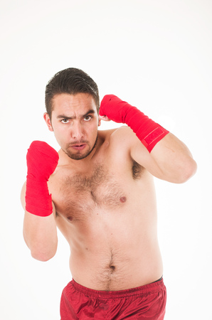 young martial arts fighter wearing red shorts and wristband defending isolated on white Stock Photo