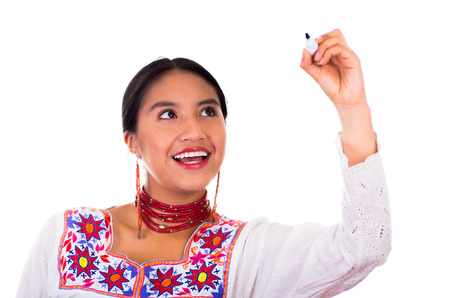 Charming young woman wearing traditional andean blouse with colorful embroideries, matching red necklace and earrings, facing camera while writing in air using marker, smiling happily, white studio background.