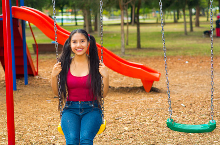 pig tails: Young pretty teenage girl with pig tails wearing jeans and purple top, sitting on swing at outdoors playground, smiling happily for camera. Stock Photo