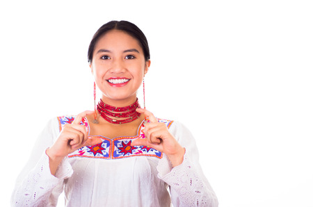 facing on camera: Charming young woman wearing traditional andean blouse with colorful embroideries, matching red necklace and earrings, facing camera while shaping retangular figure using hands, smiling happily, white studio background.