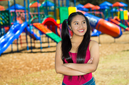 pig tails: Young pretty teenage girl with pig tails wearing jeans and purple top, standing in front of outdoors playground, smiling happily for camera.