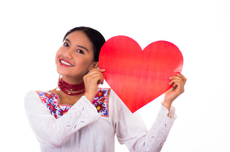 Charming young woman wearing traditional andean blouse with colorful embroideries, matching necklace and earrings, facing camera while holding red heart figure, smiling happily, white studio background.