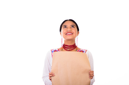 facing on camera: Charming young woman wearing traditional andean blouse with colorful embroideries, matching necklace and earrings, facing camera while holding brown paper sheet, white studio background. Stock Photo
