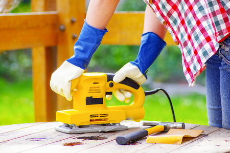 filings: hands holding a eletric sander while sanding a table.