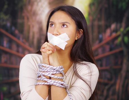 手首と口を覆っている、カメラ、人質の概念に直面している白いテープの周りにロープで縛られ若いブルネットの女性。 写真素材