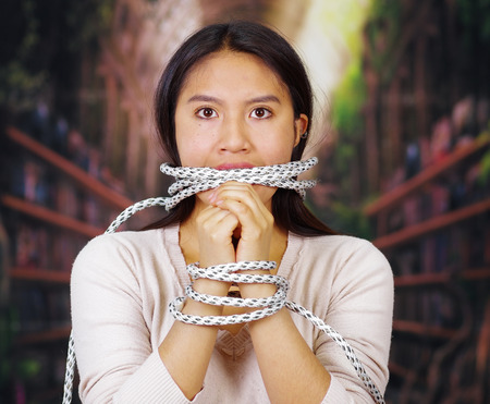 facing on camera: Young brunette woman wearing white sweater tied up with rope around wrists and gagged mouth, facing camera, hostage concept. Stock Photo