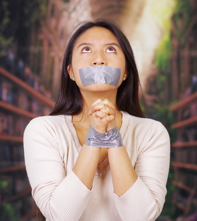 facing on camera: Young brunette woman wearing white sweater gagged and tied with duct tape around wrists, facing camera, hostage concept. Stock Photo