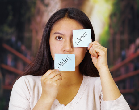 Young brunette woman wearing white sweater facing camera, partly covering face with paper notes reading help and silence, hostage concept.