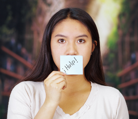 Young brunette woman wearing white sweater facing camera, partly covering face with paper note reading help, hostage concept.