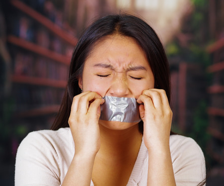 raped: Young brunette woman wearing white sweater gagged with duct tape covering mouth, facing camera, hostage concept. Stock Photo
