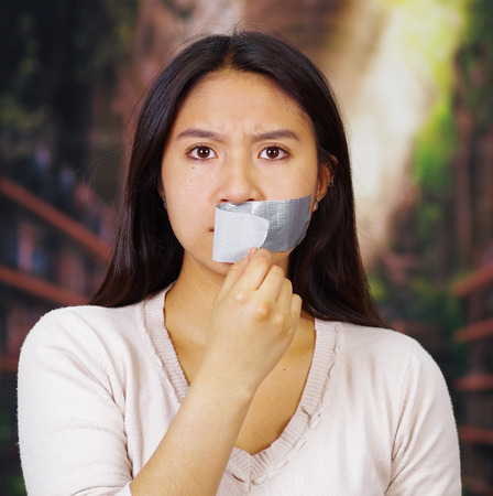 Young brunette woman wearing white taking off duct tape covering mouth, facing camera, hostage concept.